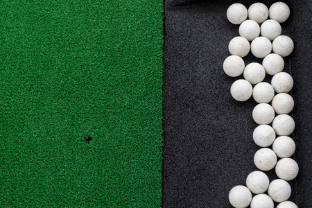Golf balls on a synthetic grass mat at a practice range.