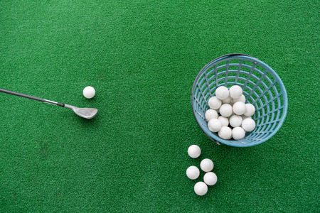 Golf club and balls on a synthetic grass mat at a practice range. Stockfoto