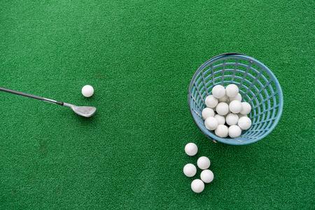 Palo de golf y pelotas sobre una estera de césped sintético en un campo de práctica.