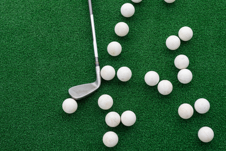 Golf club and balls on a synthetic grass mat at a practice range. Imagens