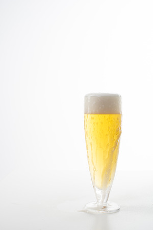 Full glass of beer set against a white background