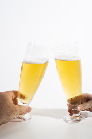 Two full glasses of beer set against a white background