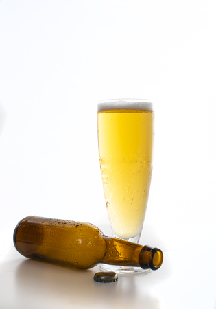 Full glass of beer and a brown bottle set against a white background Imagens