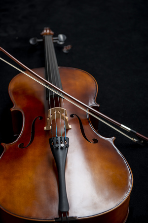 Close up of a cello and a bow set against a black background