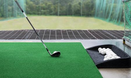 Palo de golf y pelota sobre una alfombra de césped sintético en un campo de práctica.