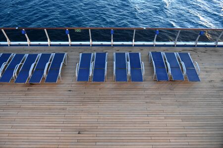Empty lounge chairs on the deck of a ship