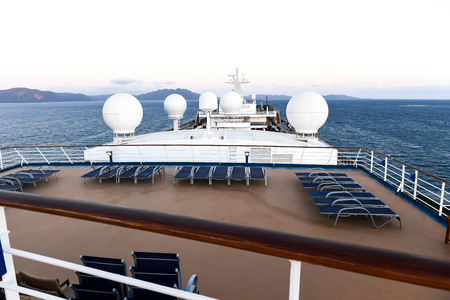 Forward view of a cruise ship overlooking lounge chairs and radar. Standard-Bild - 118178624