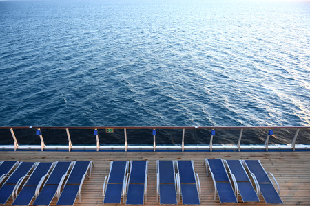 Lounge chairs on a ships deck with the ocean in the background.