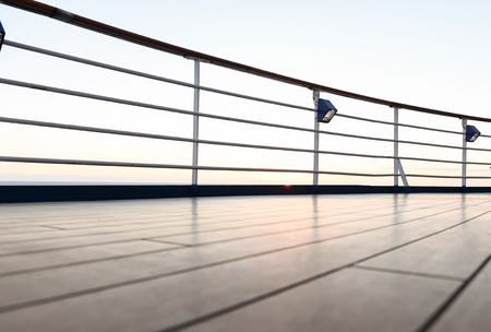 Railing and deck flooring of a cruise ship at sunset with the ocean in the background. Imagens