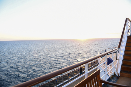 Railing and deck flooring of a cruise ship at sunset with the ocean in the background. 版權商用圖片