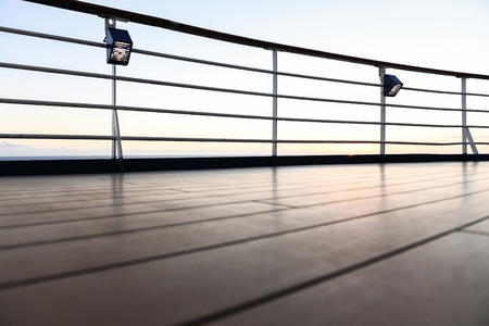 Railing and deck flooring of a cruise ship at sunset with the ocean in the background. Stok Fotoğraf