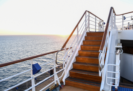 Railing and stairs of a cruise ship at sunset. Imagens