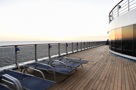 Railing and deck flooring of a cruise ship at sunset. Standard-Bild - 118397953