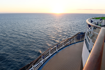 Railing and deck flooring of a cruise ship at sunset.