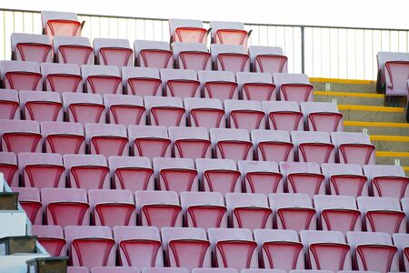 Empty multi-coloured seats at a sporting venue.