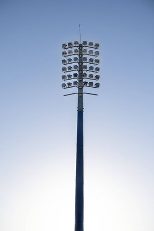 Sports stadium light tower during the day, set against a blue sky. 版權商用圖片