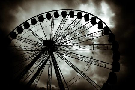 Ferris wheel against a dark cloudy sky. Фото со стока