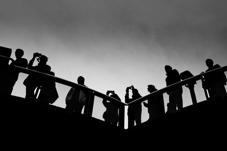 A group of people stand in silhouette, against a dark sky on a viewing platform at Katoomba, New South Wales.
