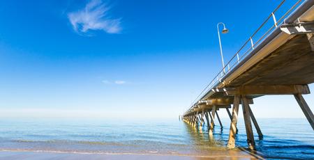Clear calm blue sky day with a long wooden pier vanishing to the horizon. Glenelg Beach, South Australia. Фото со стока