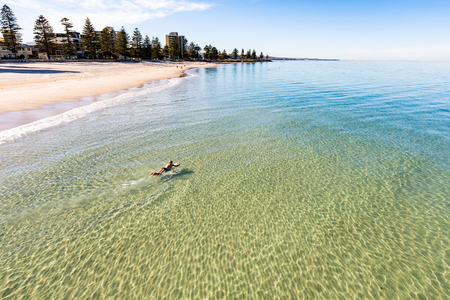 A lone swimmer paddles out on his surfboard in the still waters of Glenelg Beach, South Australia.
