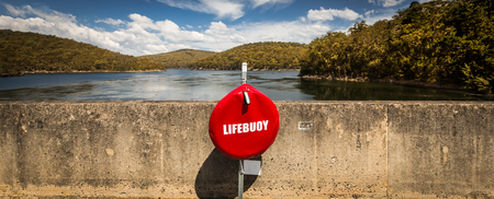 Bright red life buoy centrally placed against a concrete wall in a wide panorama with a blue lake and green hills in the background on a sunny blue sky day.