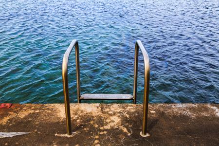 A chrome steel ladder leads into an ocean pool, South Coast, NSW, Australia.