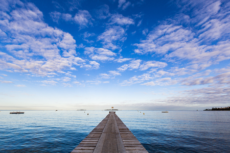 A symmetrical early morning landscape photo with a low horizon, looking along a wooden pier to the calm blue waters of Anse Vata Bay, Noumea, New Caledonia.