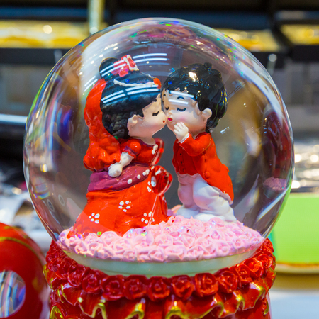 Boy and girl figures kissing on top of a wedding cake under a souvenir snow dome.