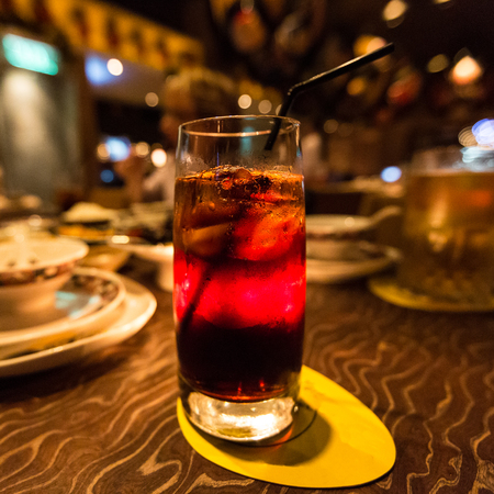 An icy cold red colored drink on the table of a Chinese restaurant in the evening. Фото со стока