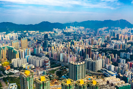 Aerial view of Hong Kong city skyline and high rise apartment blocks, viewed to the distant mountains.