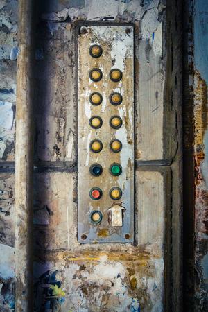 Old and dirt buttons serve as an apartment block intercom system. Hong Kong.