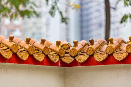 Golden colored glazed ceramic ridge tiles adorn a wall. Hong Kong.