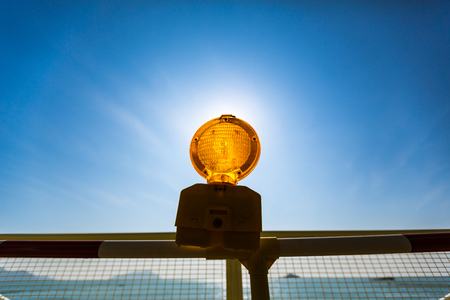 The golden lens of a construction site lamp anginst a blue sky and bight sun.