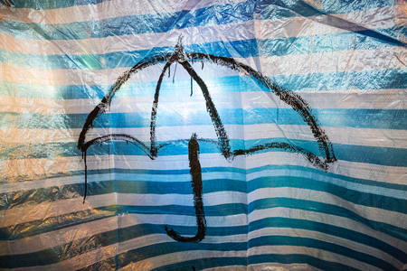 A painted black umbrella symbol on a blue striped tarpaulin. Part of the Umbrella Protest in Hong Kong. December 2013.