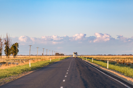 A truck approaches on a long, straight single lane highway in rural New South Wales. Фото со стока