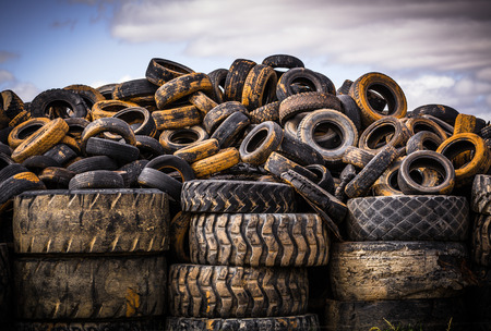 Pile of old used car and truck tires against an afternoon sky.