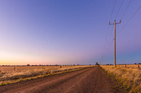 A dirt road tand row of power poles hrough farmland at sunset. Central Victoria. Фото со стока