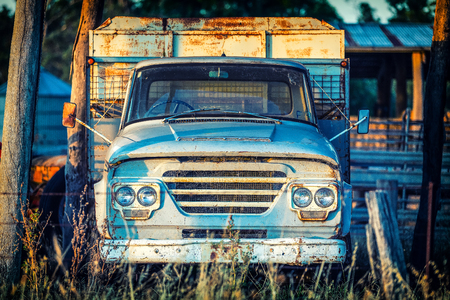 Old rusty blue farm truck in late afternoon light at sunset.  Central Victoria.