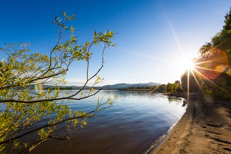 View from the shore of Lake Jindabyne in the New South Wales Snowy Mountains on a crisp clear morning, looking into the sun. Фото со стока