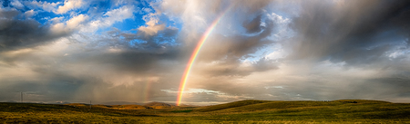 Panoramic view of a late afternoon thunderstorm and rainbow across rolling hills. Southern New South Wales.