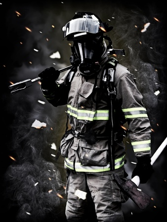 Aftermath , A firefighter Poses after a long fire fight with smoke,debris, and embers in the background. For more firefighter images please visit my profile.  Stock Photo - 10750162