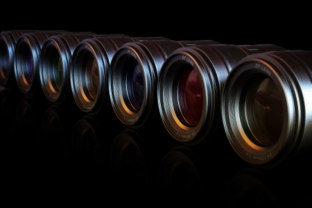 slr cameras: Camera lenses in a row with different color lenses with reflection.  Stock Photo