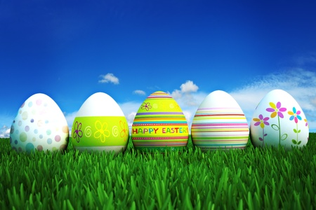Happy Easter, colored eggs in a grass field with a clear blue sky. Room for text and copy space