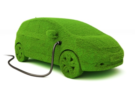 electric automobile: Alternative power concept eco car . Grass covered car plugged into power supply on a white background.  Stock Photo