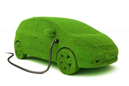 eficiencia: Concepto de alimentación alternativas coche ecológico. Grass cubierto enchufado coches en la fuente de alimentación en un fondo blanco. Foto de archivo