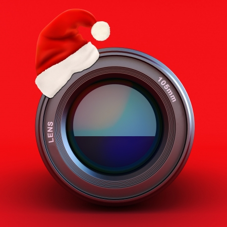 Camera lens with Santa hat on a red background  photo
