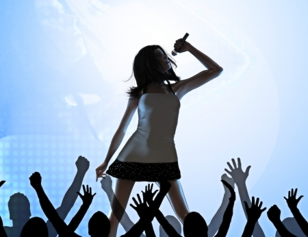 stage performer: Female singer on stage performing infront of a crowd