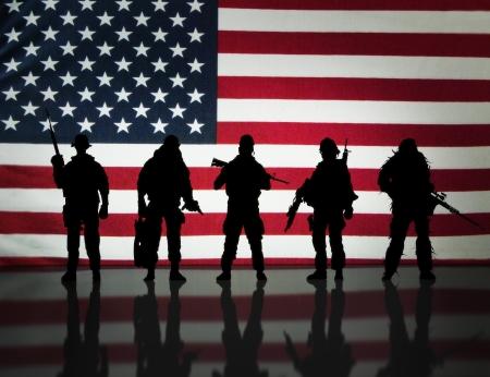 delito: Fuerzas especiales militares estadounidenses silueta s posando delante de una bandera americana
