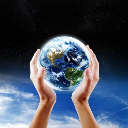 hidrógeno: Concepto de ahorro de la Tierra, las manos sosteniendo la tierra con el cielo y el fondo del espacio Foto de archivo