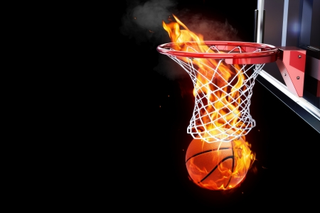room for text: Flaming basketball going through a court net  Room for text or copy space on a black background  Stock Photo